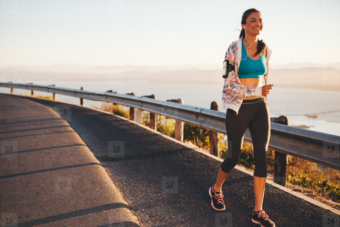 Happy young woman running on country road