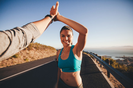 Man and woman high fiving after running training