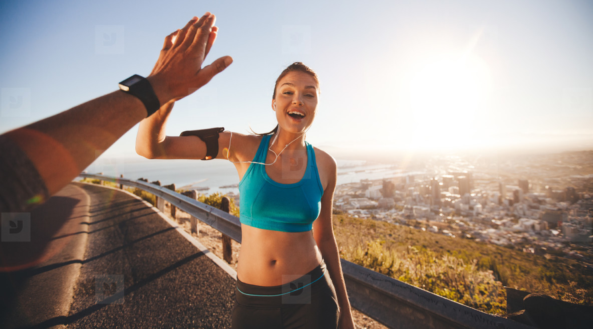 Fit young woman high fiving her boyfriend after a run