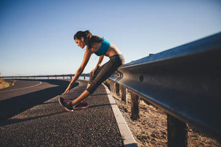 Young woman doing stretching after a run
