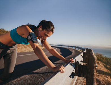 Tired runner taking a break leaning guardrail