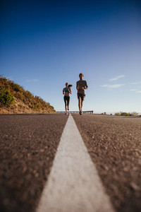 Two young people jogging on the road