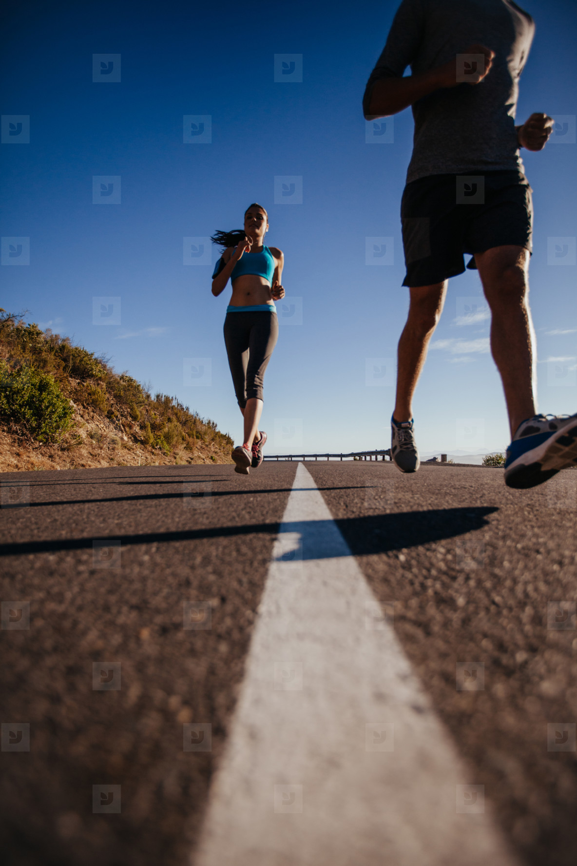 Woman running on road with man in front