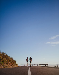 Two young runners running on open country road
