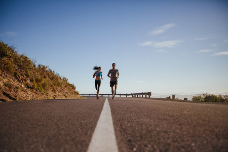 Joggers jogging together on country road