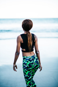 Back view of woman in sports wear at beach