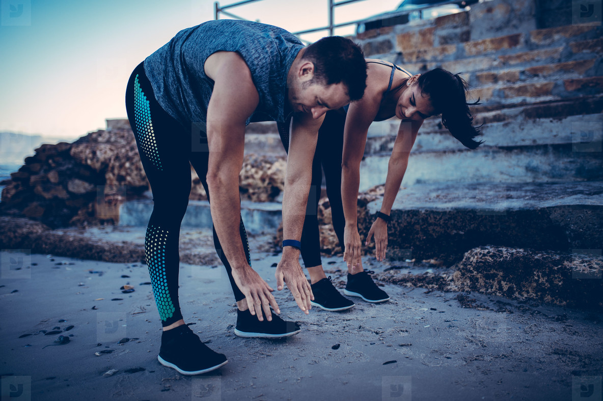 Young athlete couple doing stretching exercise together