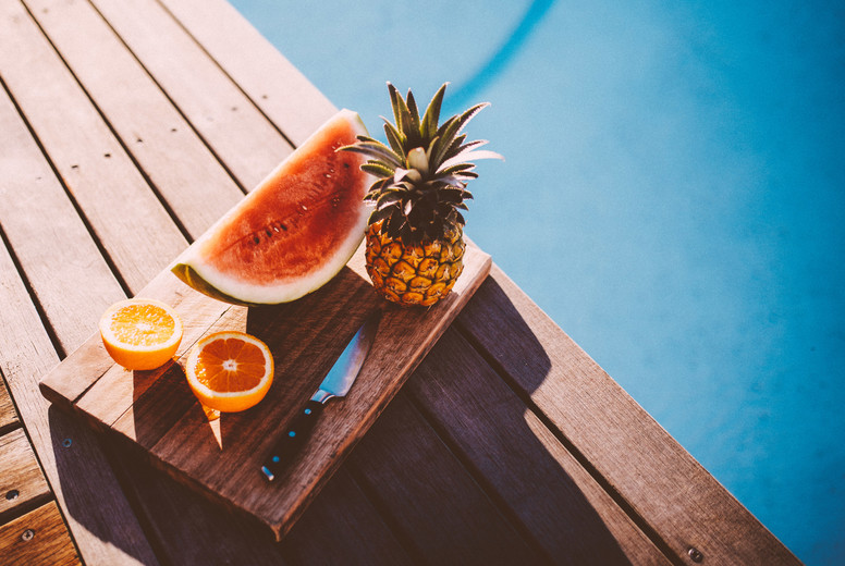 Plate with Tropical fruits next to swimming pool