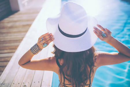 Back view of attractive woman wearing a summer hat