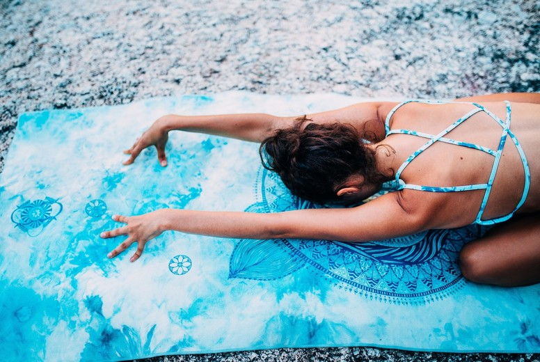 Back view of woman lying on yoga towel