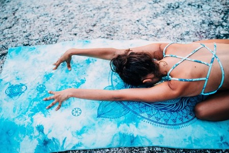 Back view of woman lying on yoga towel
