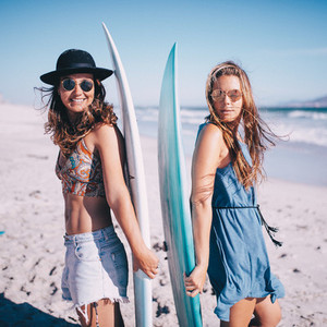 Portrait of two young woman with surfboards on beach