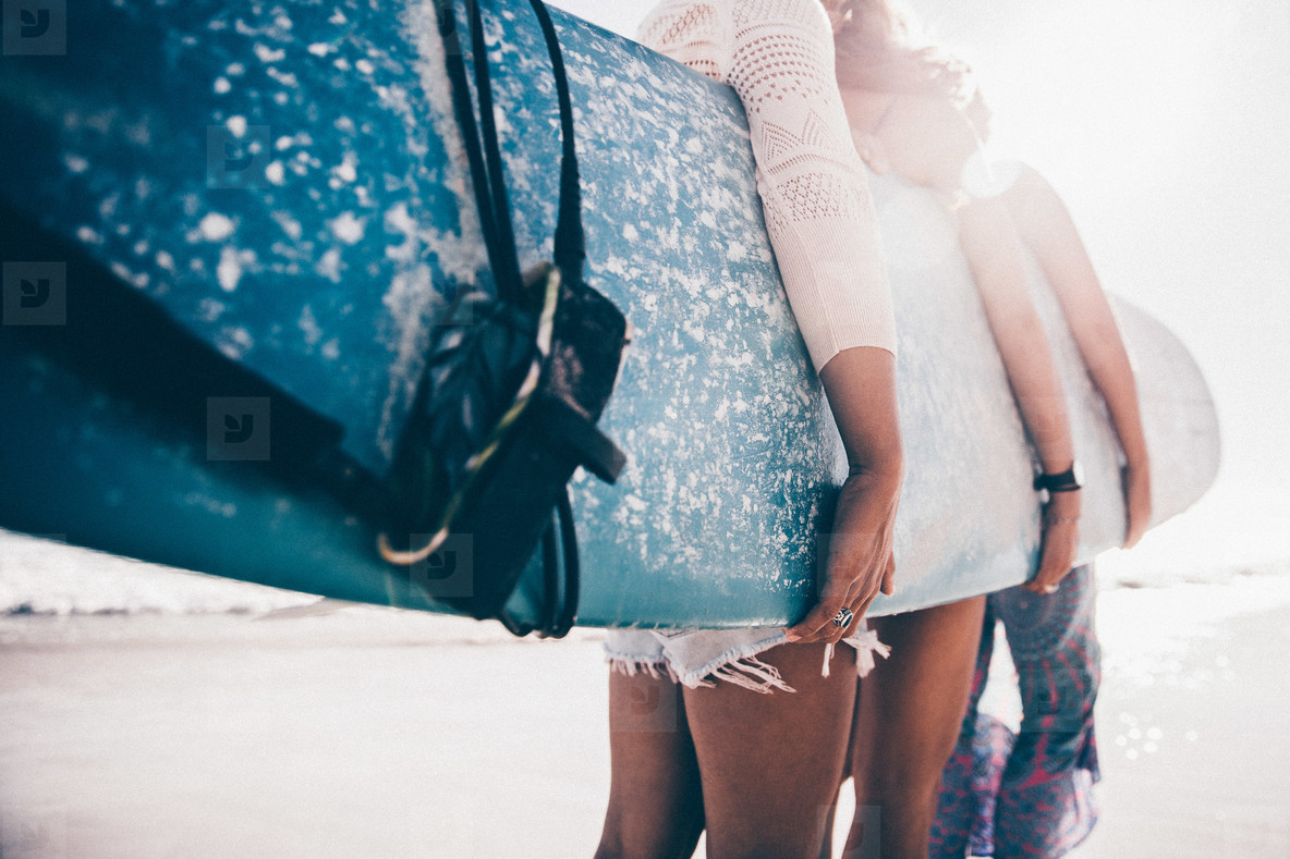 Group of girls holding surfboard on beach