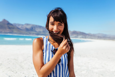Young woman at the beach and smiling