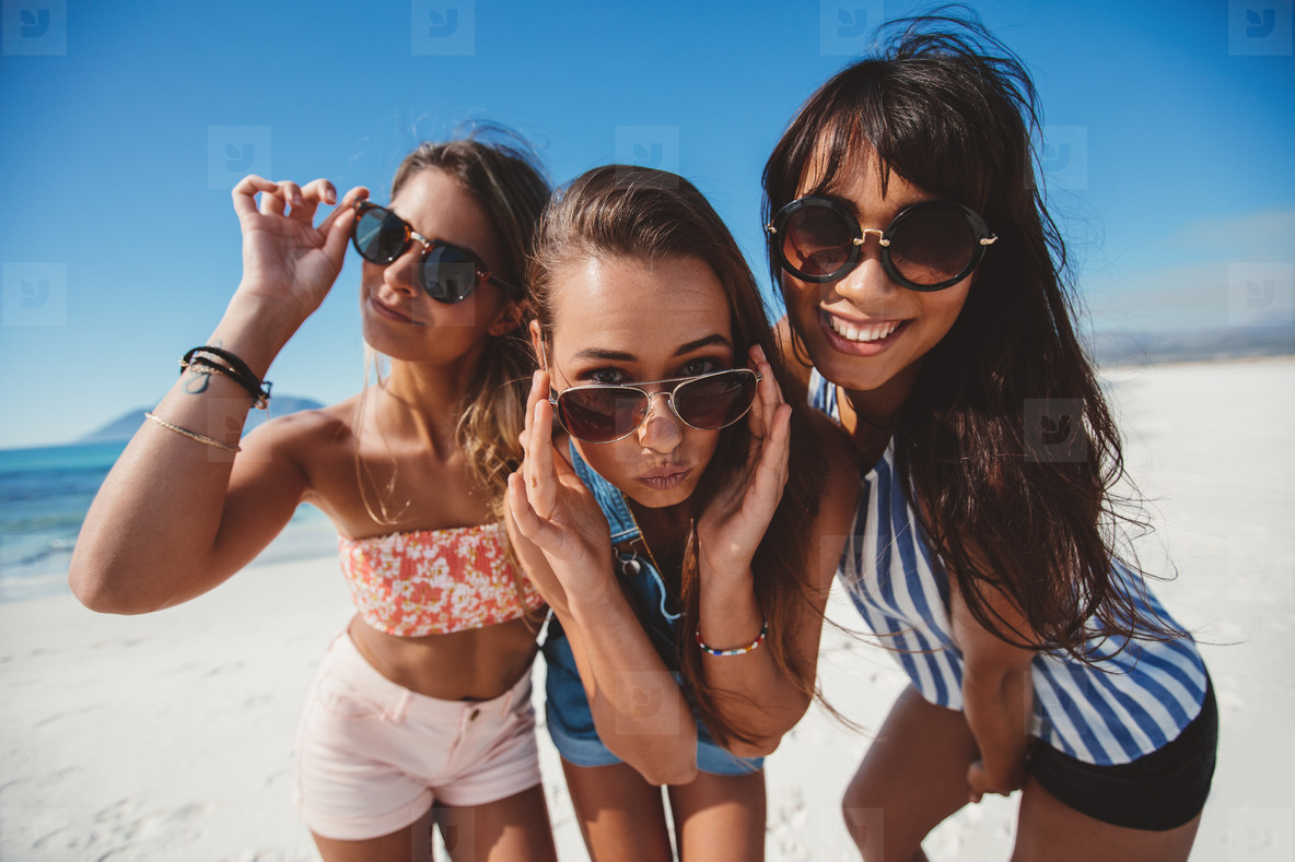 Women friends in sunglasses posing at the beach