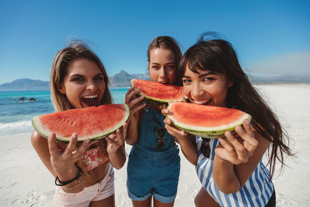 Three young women enjoy fresh watermelon on beach