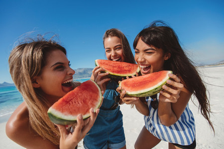 Female friends laughing and eating watermelon on the shore
