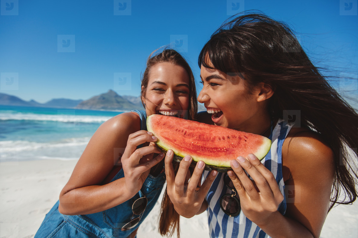 Young women enjoying watermelon on beach vacation