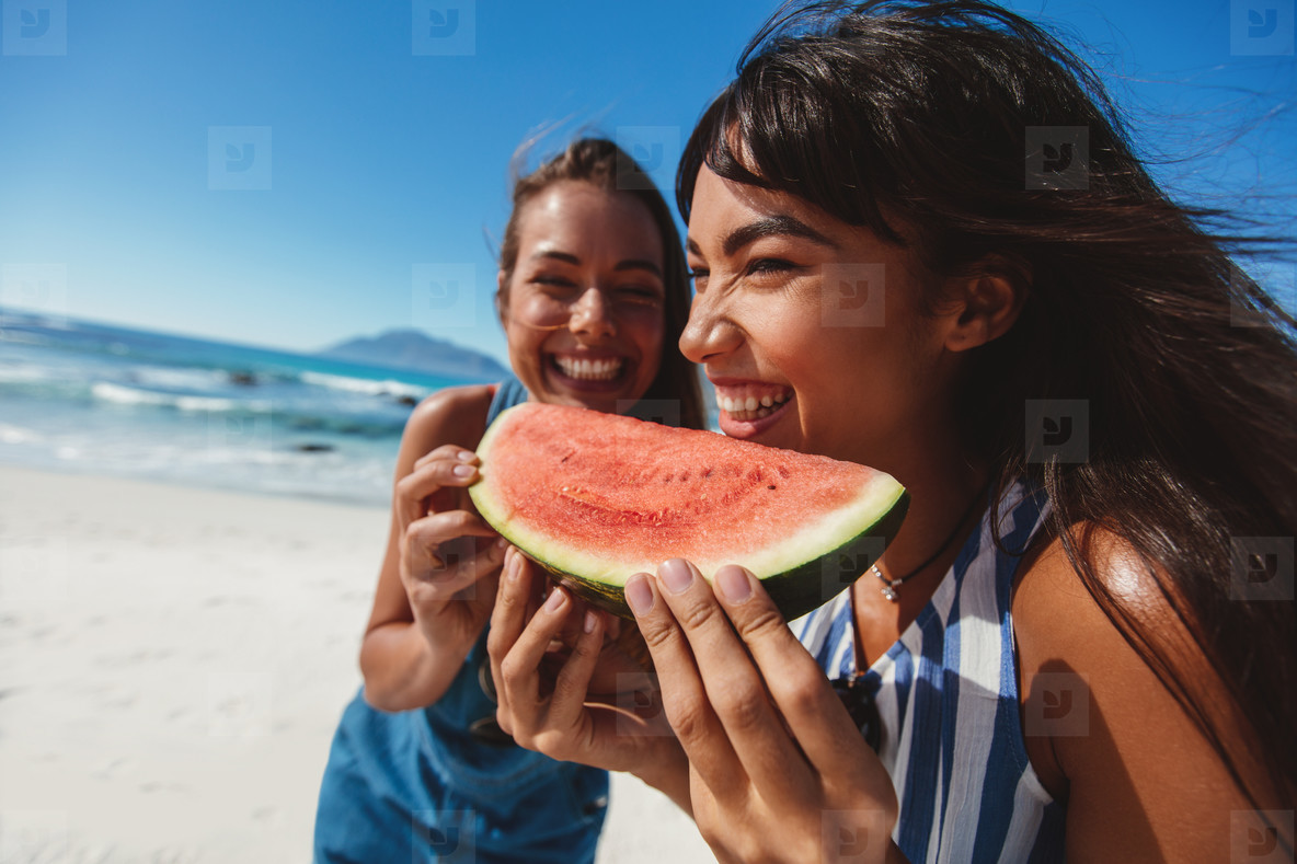 Female friends eating watermelon at the shore