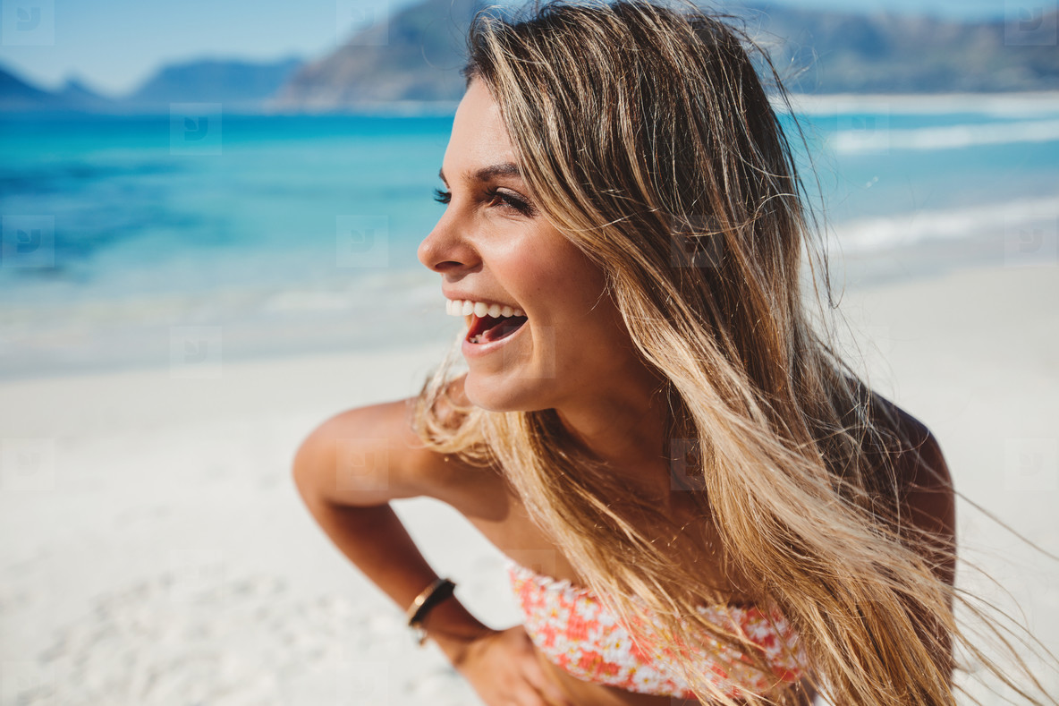 Attractive young woman laughing on the beach
