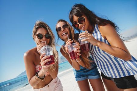Female friends on the beach drinking ice tea