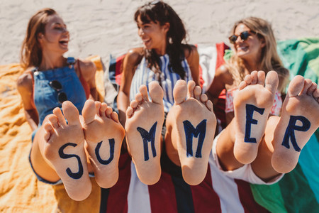 Word summer on the feet of young women at the beach