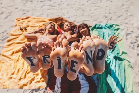 Word friends on the feet of young women lying at the beach