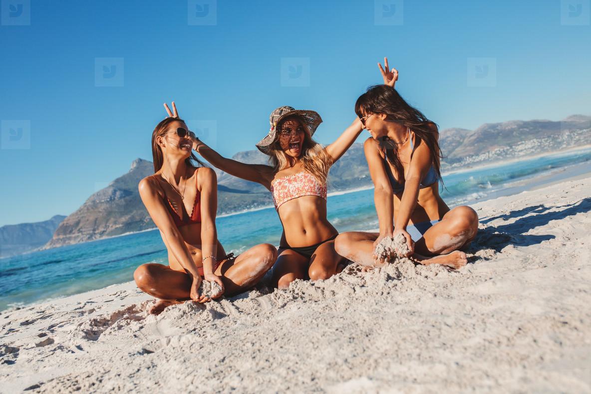 Smiling young women having fun on the beach