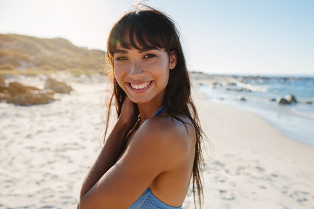 Smiling young woman in bikini on the beach