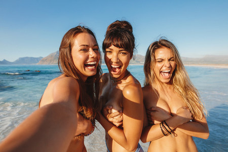 Topless young women on the beach taking selfie