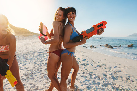 Playful young women having fun on beach with water gun