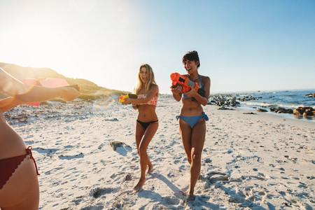 Young women having fun on the beach with water gun fight