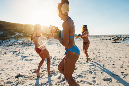 Three young women in bikini having water gun fight on beach
