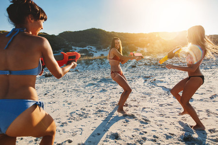 Girls with water pistols playing on the beach