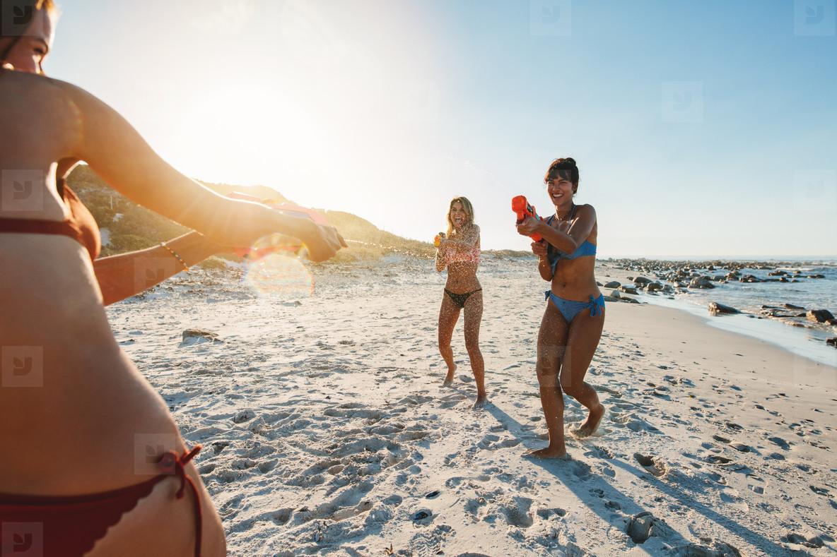 Group of women having water gun fight on beach
