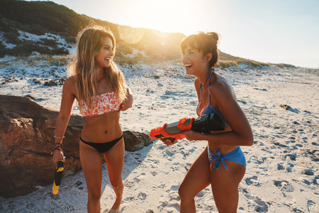 Joyful friends playing with water pistols on the beach