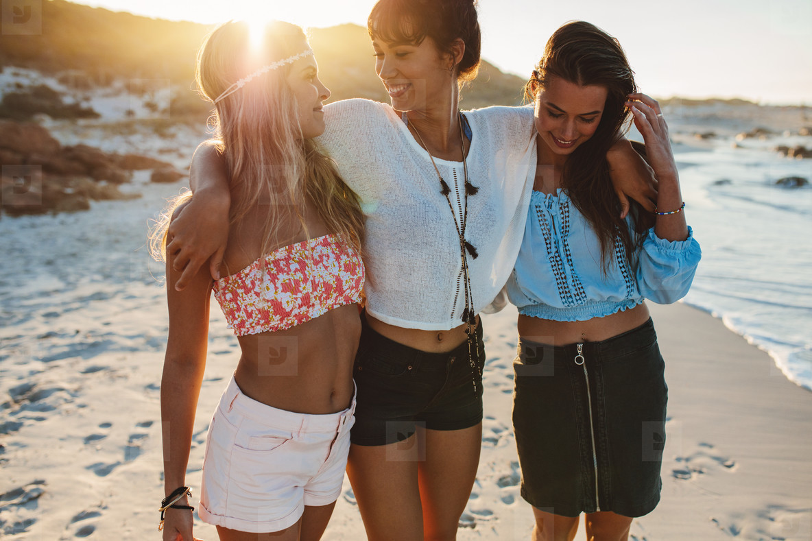 Happy young women strolling along coastline