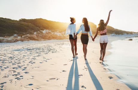 Young females walking along the beach on a summer day