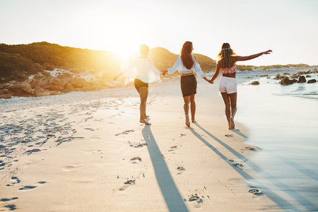 Young women strolling along a beach and enjoying