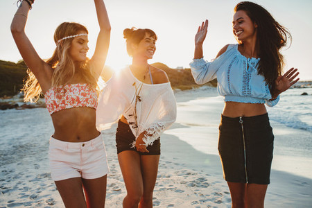 Female friends dancing together at the beach