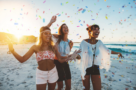 Female friends partying on the beach with confetti
