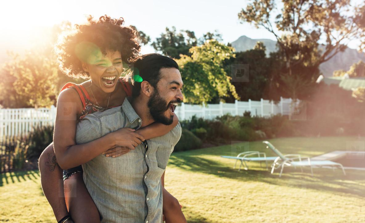 Young couple piggybacking in backyard