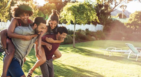 Couples piggyback ride race in backyard