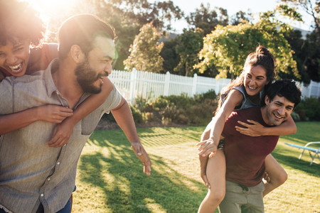 Couples playing piggyback ride race