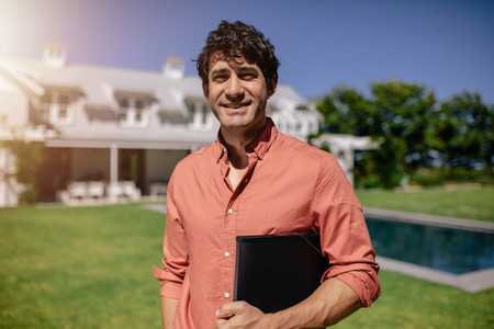 Real estate agent standing outside a home for sale