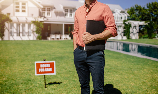Male real estate broker outside a house for sale