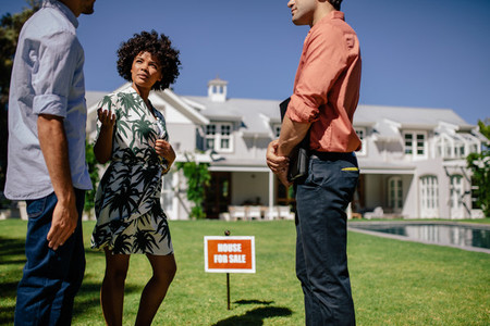 Young couple with real estate agent visiting house for sale