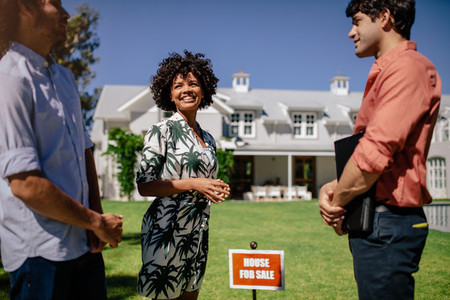 Couple with real estate agent visiting house for sale