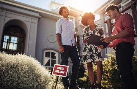 Home buyers with broker going through paper work