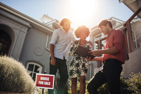 Real estate agent with couple buying new house